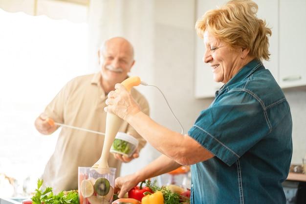 Счастливые старшие пары подготавливая завтрак с фруктом и овощем. здоровый образ жизни и радостное пожилое понятие