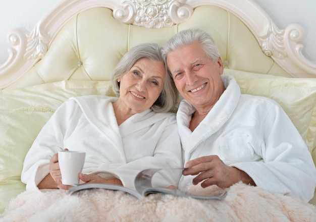 Happy senior couple reading in bed  with magazine