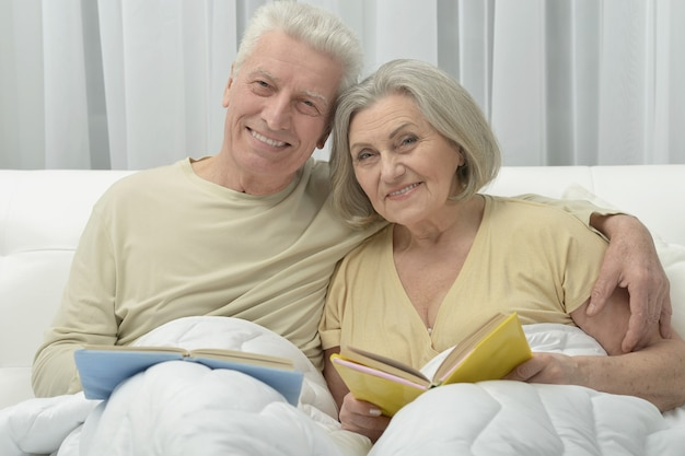 Happy senior couple reading in a bed