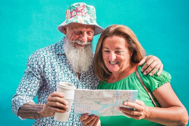 Happy senior couple reading city map - old tourist people having fun traveling around the world