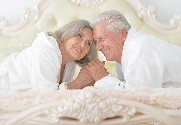 Счастливая старшая пара, читающая в постели
