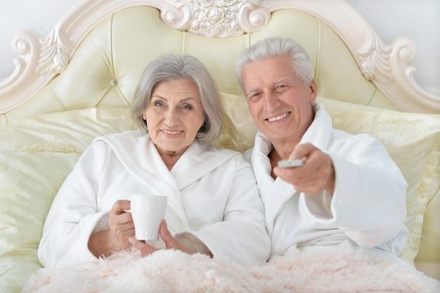 Счастливая старшая пара, читающая в постели, смотря телевизор