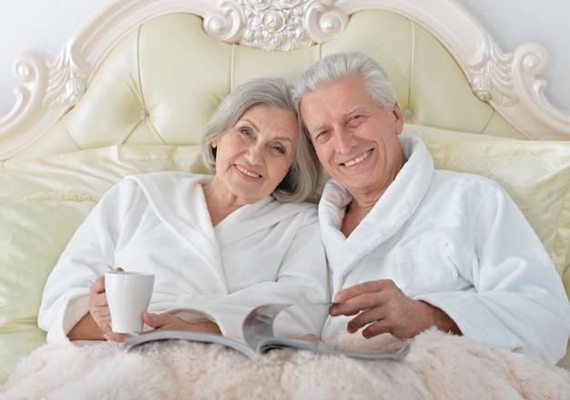 Счастливая старшая пара, читающая в постели с журналом