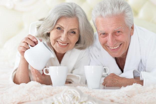 Счастливая старшая пара, читающая в постели с чаем