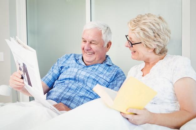 Happy senior couple reading newspaper