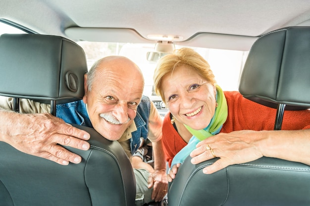 Happy senior couple ready for driving car on journey trip