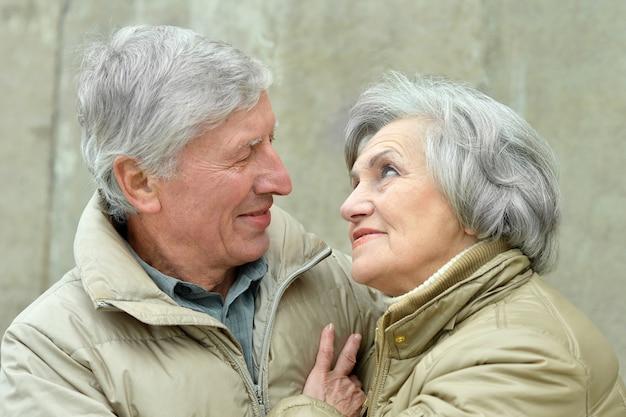 幸せな年配のカップルは秋の公園でリラックス