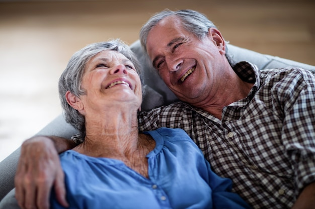 Happy senior couple relaxing on sofa and smiling