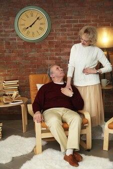 家で休んでいる幸せな年配のカップル