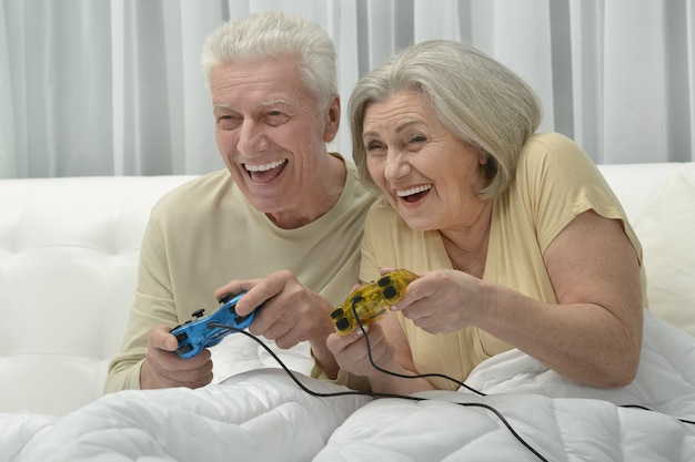 Happy senior couple resting in bed playing video game