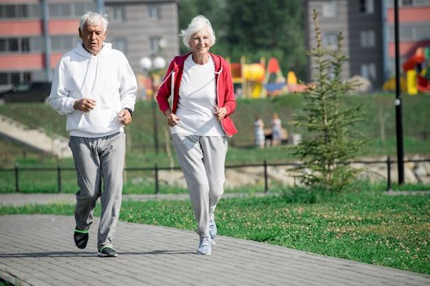 公園で走っている幸せな先輩カップル