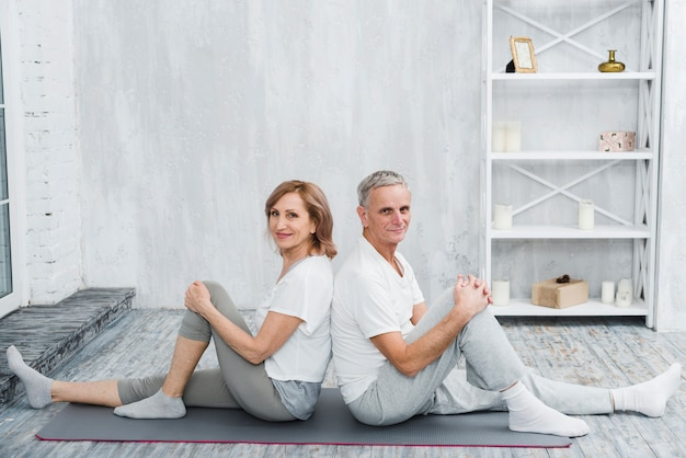 Happy senior couple sitting back to back on grey yoga mat