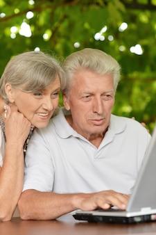 Счастливая пара старших, сидя летом за столом с ноутбуком