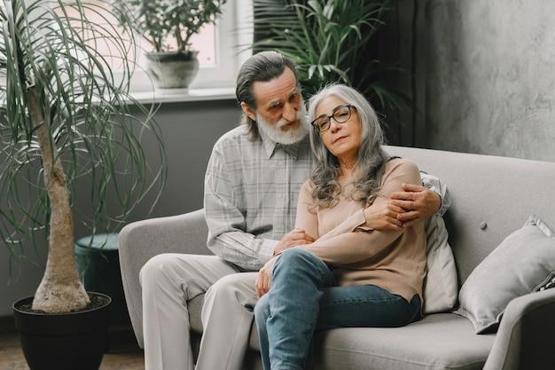 自宅のソファに座って話している幸せな年配のカップル。質の高い時間の概念。