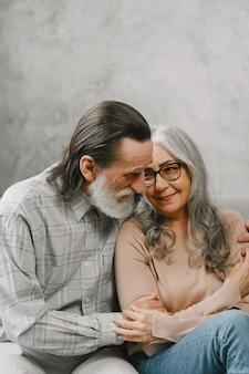 自宅のソファに座って話している幸せな年配のカップル