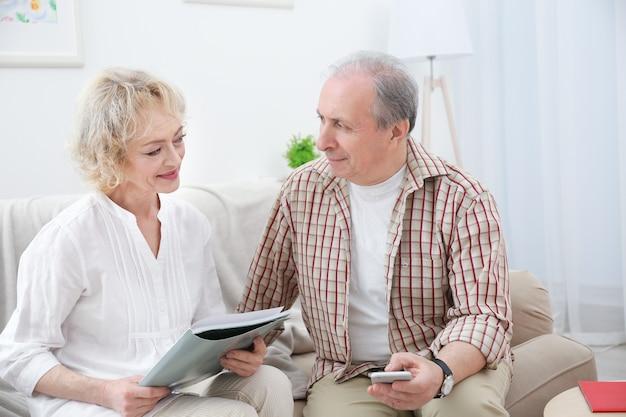 Счастливая пара старших, сидя на диване у себя дома