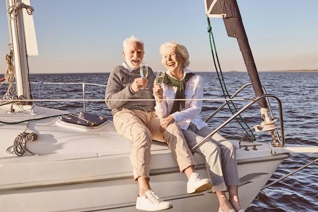 海の男と女に浮かぶ帆船やヨットのデッキの横に座って幸せな年配のカップル