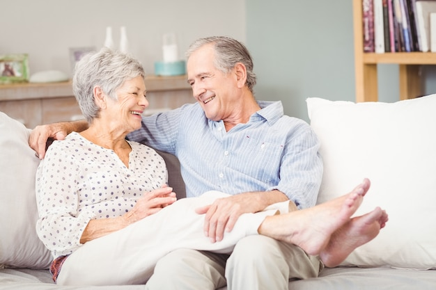 Happy senior couple sitting on sofa in living room