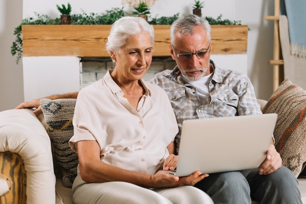 Happy senior couple sitting on sofa looking at laptop