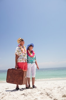 Happy senior couple standing on beach with suitcase