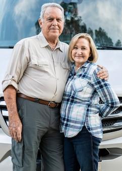 Happy senior couple standing in front of camper van