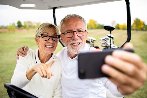 Счастливая пара старших, делающая селфи фото для социальных сетей на поле для гольфа.