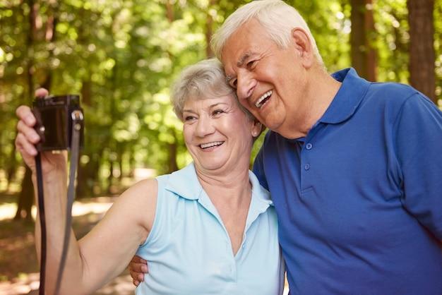 ヴィンテージカメラで自分撮りを撮る幸せな年配のカップル