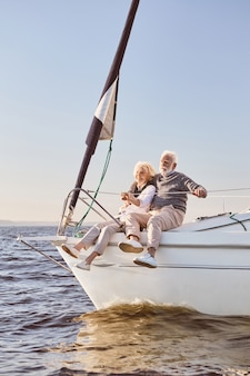 A happy senior couple talking sitting on the side of a sail boat on a calm blue sea man hugging his