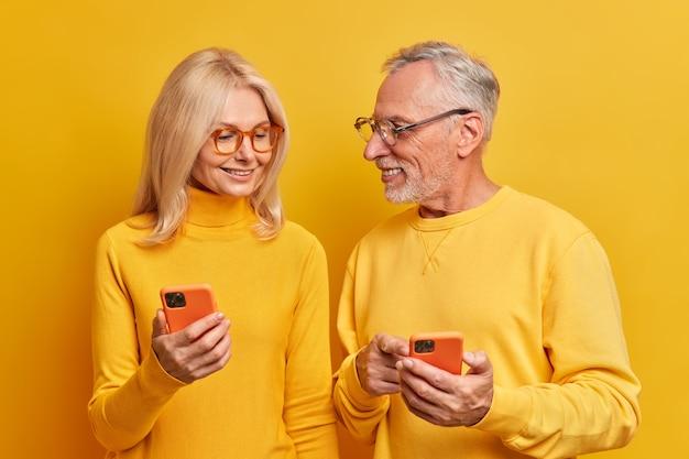 행복한 노인 부부는 집에서 휴대 전화를 사용하여 생생한 노란색 벽에 포즈를 취하는 즐거운 이야기를 착용하십시오.