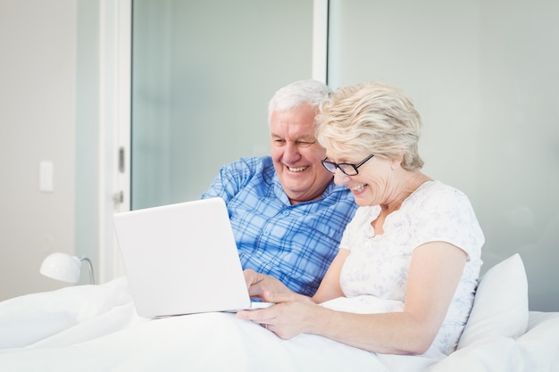 Happy senior couple using laptop on bed