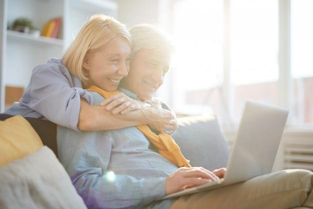 Счастливая пара старших, используя ноутбук в солнечном свете