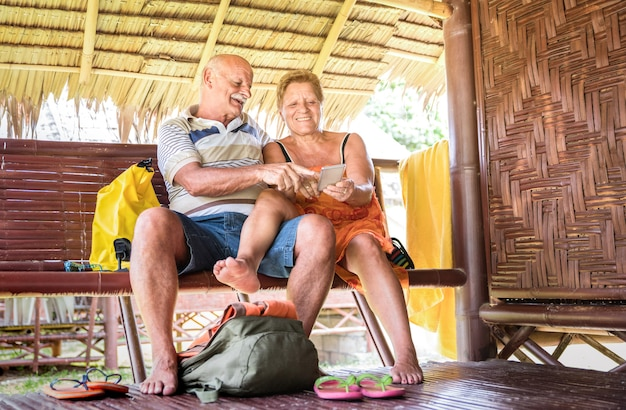 Happy senior couple using mobile smart phone at relax moment in travel resort
