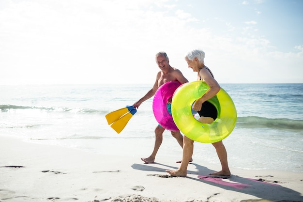 Happy senior couple walking on beach with inflatable rings and flippers
