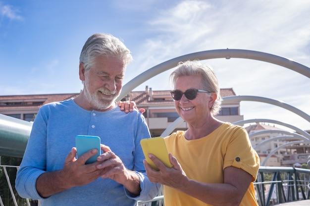 街の橋の上を歩いて幸せな年配のカップル。自分の携帯電話を見て笑っている。高齢者の現代的で技術的な