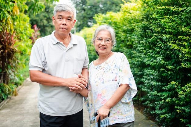 庭で一緒に歩いて幸せな年配のカップル。杖を使った老人