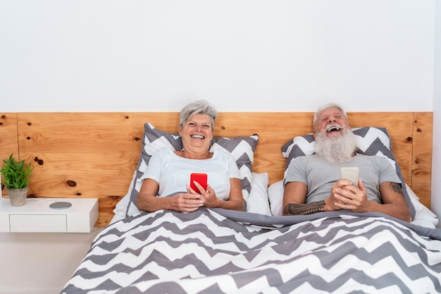 Happy senior couple watching videos with mobile phones while laughing together
