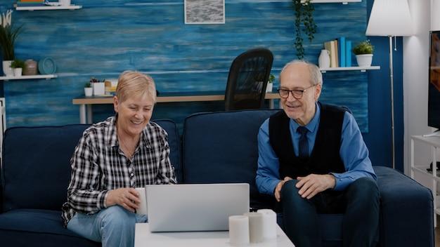 Счастливая пара старших машет на видеозвонке с племянниками, используя ноутбук, сидя на диване в гостиной