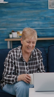 Счастливая старшая пара машет на видеозвонок с племянниками, используя ноутбук