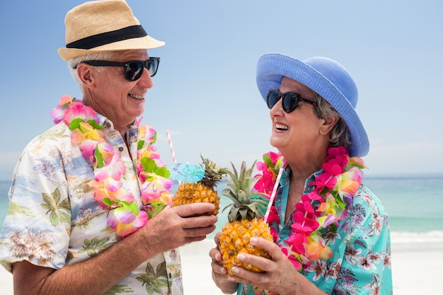 Happy senior couple wearing a garland and holding pineapple cocktail