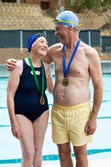 풀 사이드에 서있는 동안 메달을 입고 행복 한 노인 부부