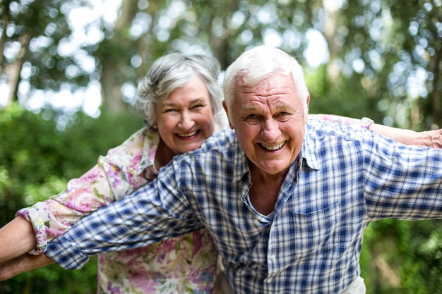 Happy senior couple with arms outstretched in back yard