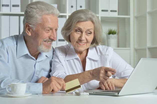 自宅でラップトップと名刺を持つ幸せな年配のカップル