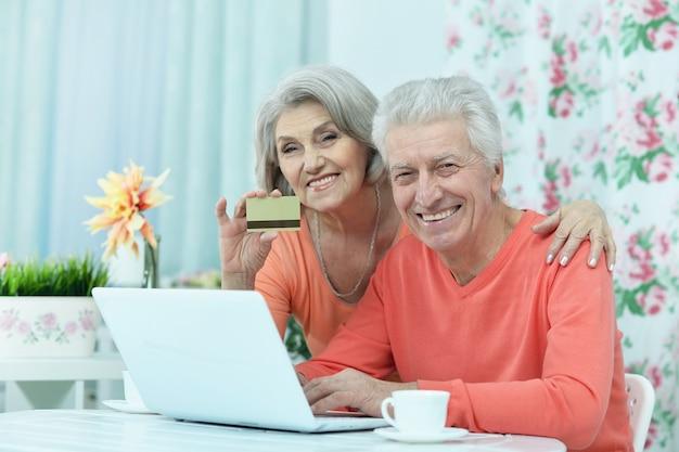 집에서 노트북과 신용 카드를 가진 행복한 노부부