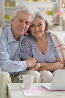 自宅でラップトップと幸せな年配のカップル