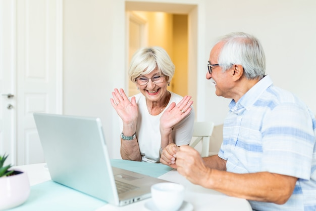 Счастливая старшая пара с ноутбуком, имеющим видеозвонок