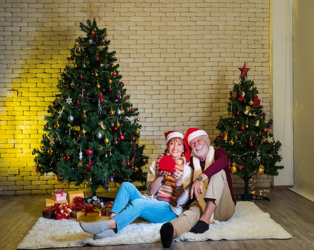 Happy senior couple with santa claus hat holding red jewelry gift box while sitting together in front of decorated christmas tree in living room. romantic winter holiday. anniversary. married.