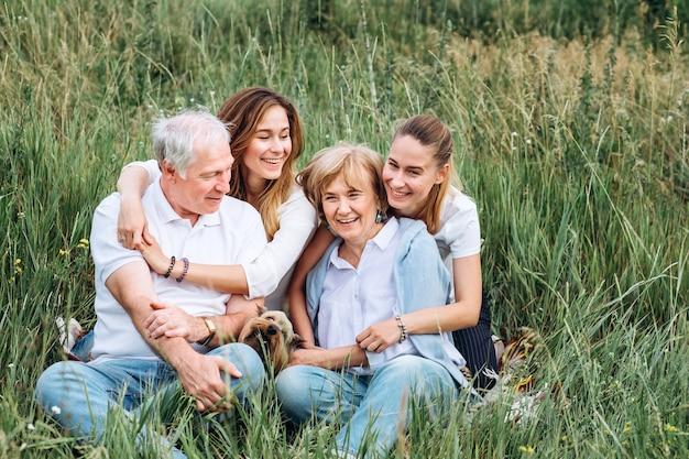 Счастливая пара старших с дочерьми на природе
