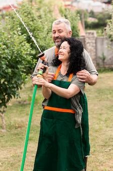 Счастливая пара старших с водой шланг