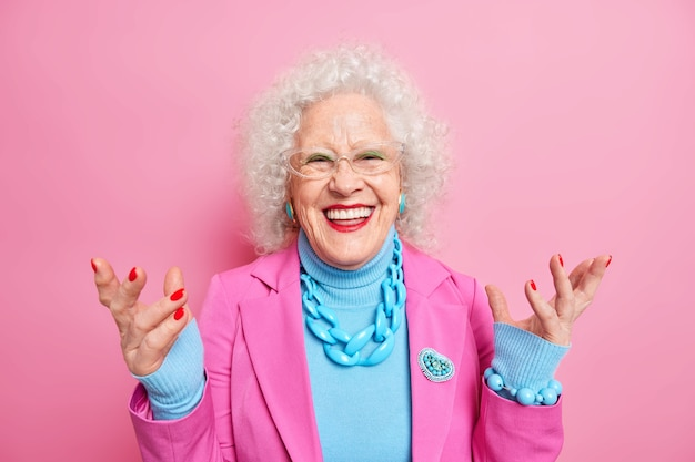 Happy senior curly woman enjoys life in old age raises hands smiles positively dressed in fashionable outfit wears bright makeup has red manicure wrinkled face