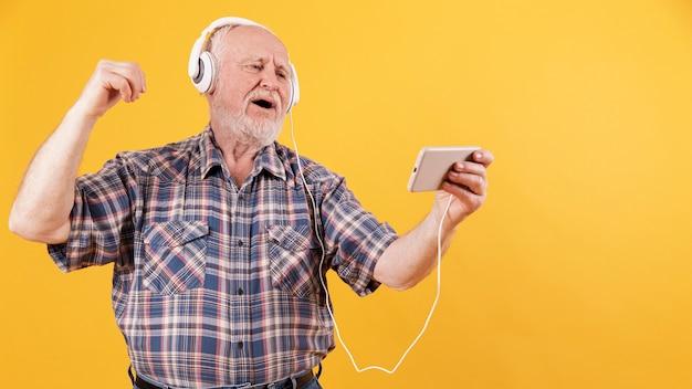 Happy senior enjoying music at home
